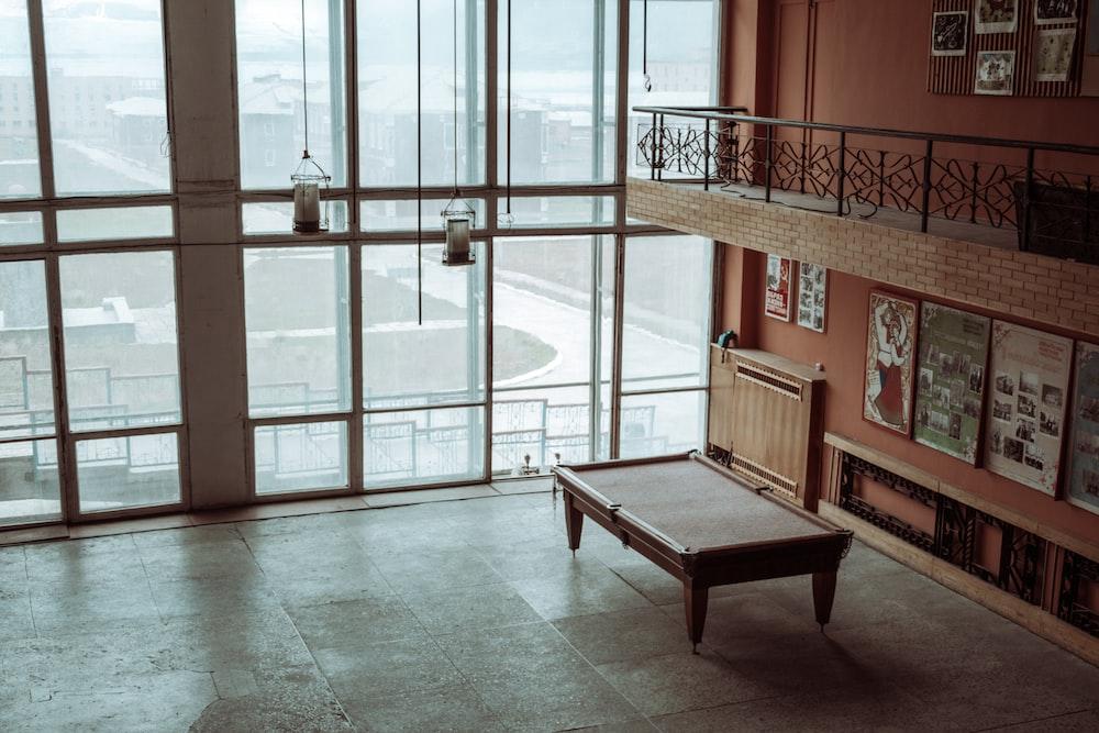 brown wooden bench near glass door