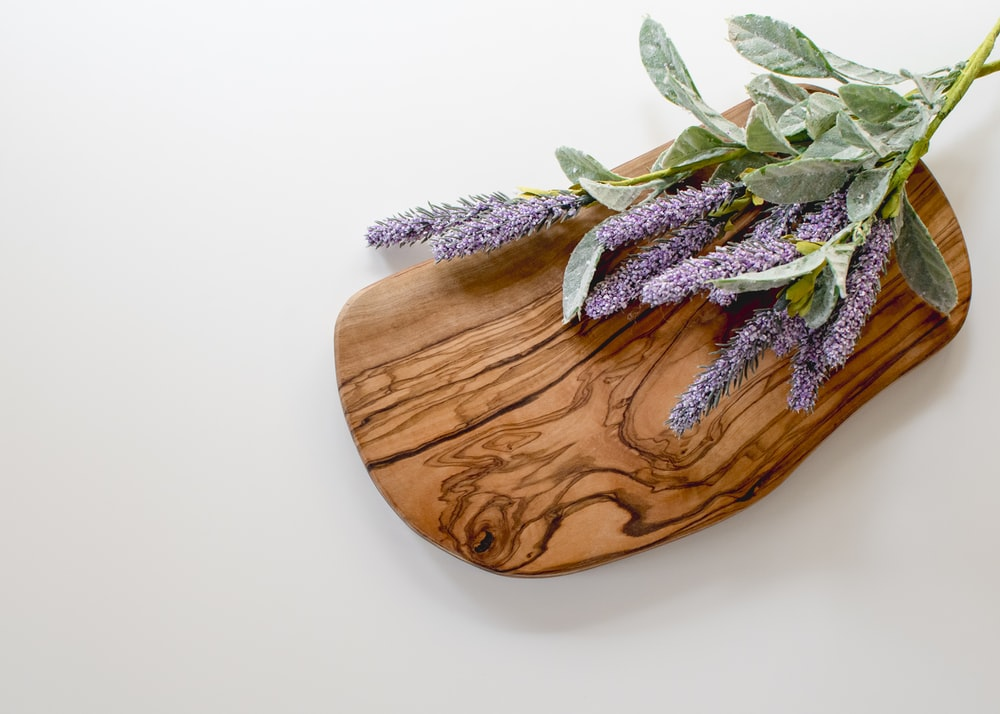 green and purple leaves on brown wooden chopping board