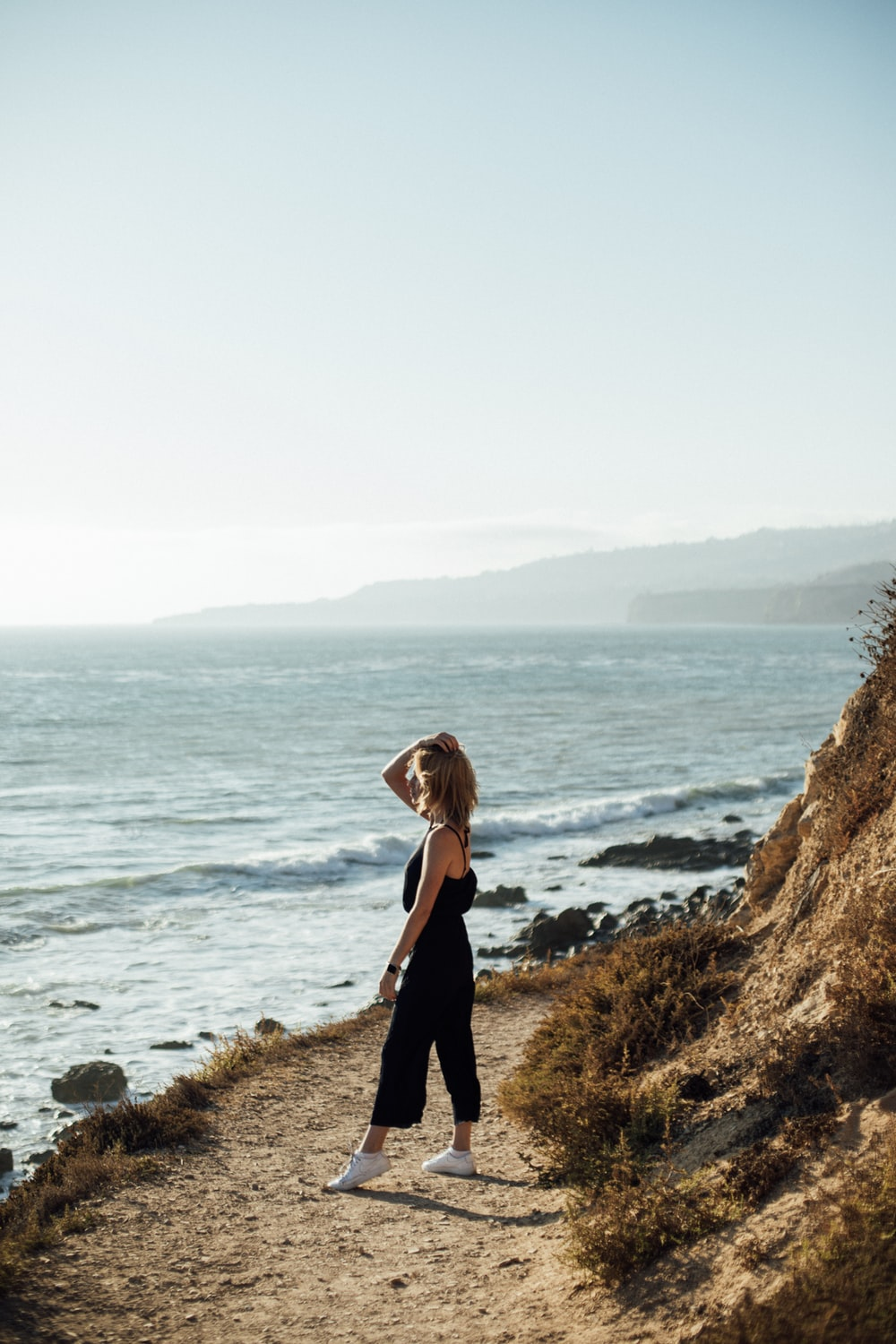 woman in black long sleeve dress standing on brown rock near body of water during daytime