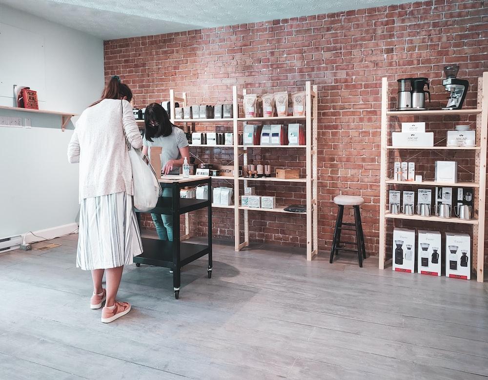 woman in white long sleeve shirt standing beside brown wooden shelf