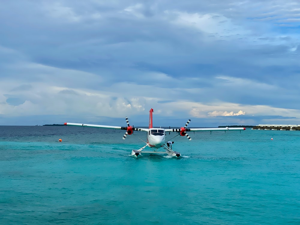 white and red airplane on sea under white clouds during daytime