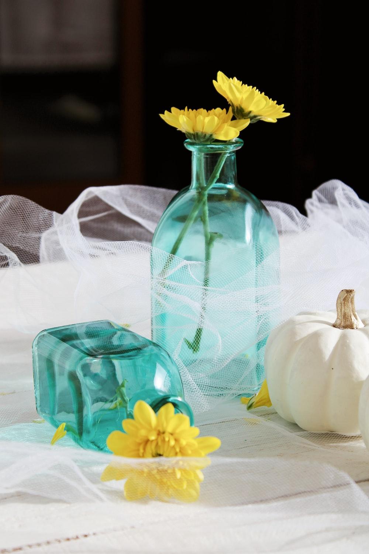 yellow flower in blue glass vase