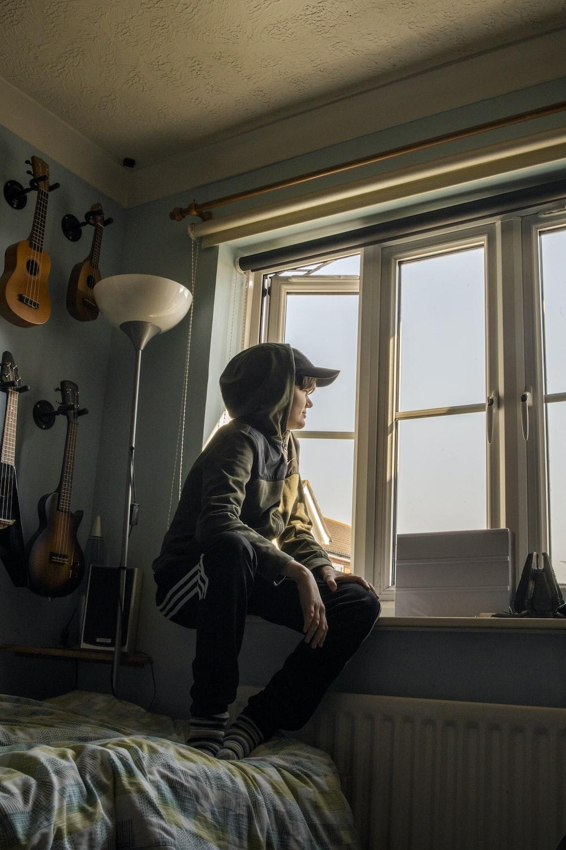 man in gray jacket sitting on chair beside window