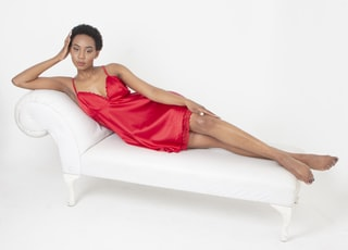 woman in red sleeveless dress sitting on white couch