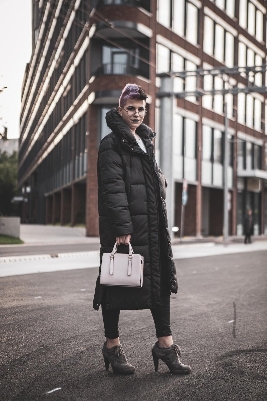 woman in black coat holding white leather handbag