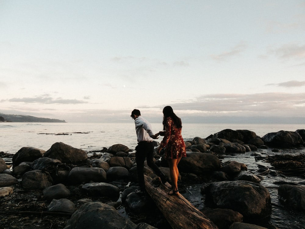 couple standing on rock near body of water during daytime