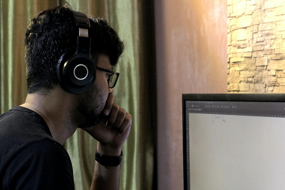 man in black crew neck t-shirt wearing black headphones