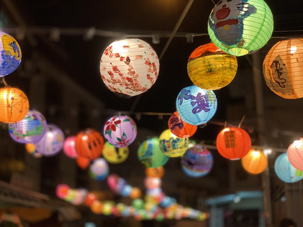 selective focus photography of assorted color hanging lanterns