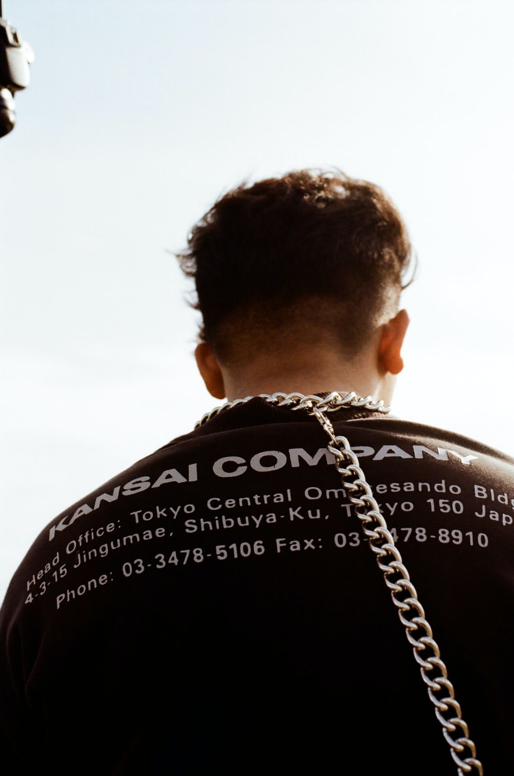 man in black shirt with silver chain necklace
