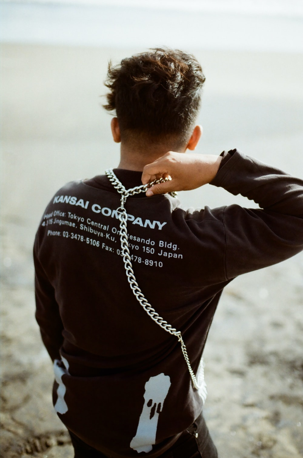 man in black long sleeve shirt wearing silver chain necklace