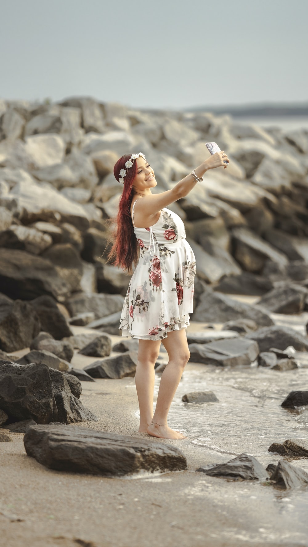 woman in white red and blue floral dress standing on gray sand during daytime