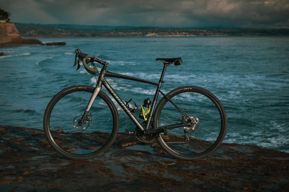 black and white mountain bike on seashore during daytime