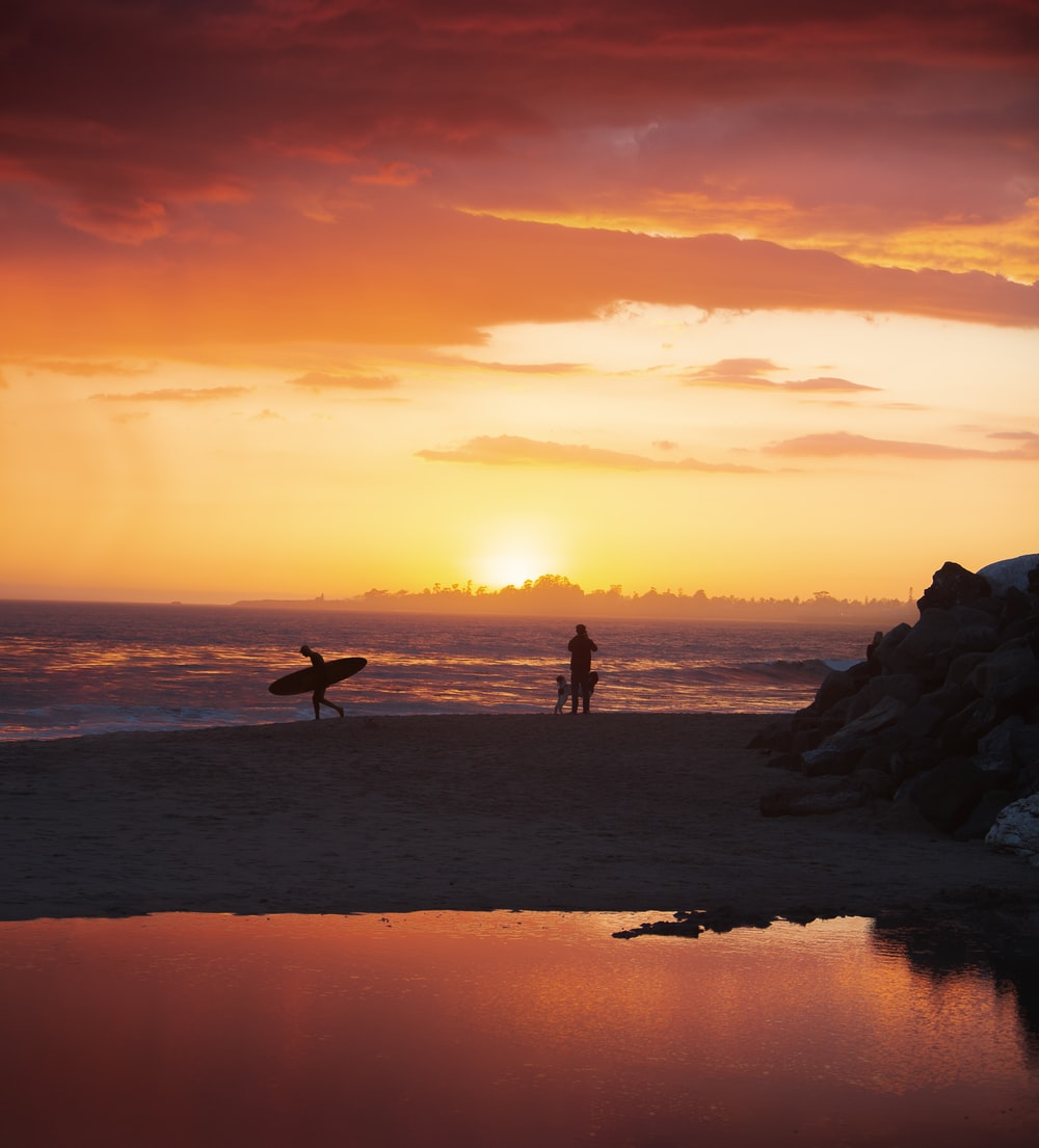 silhouette of 2 people standing on rock formation near sea during sunset