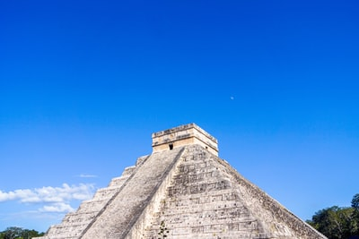 gray concrete building under blue sky during daytime mayan pyramid teams background