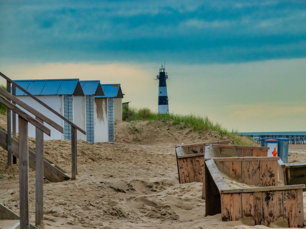 white and blue wooden house on brown sand under blue sky during daytime