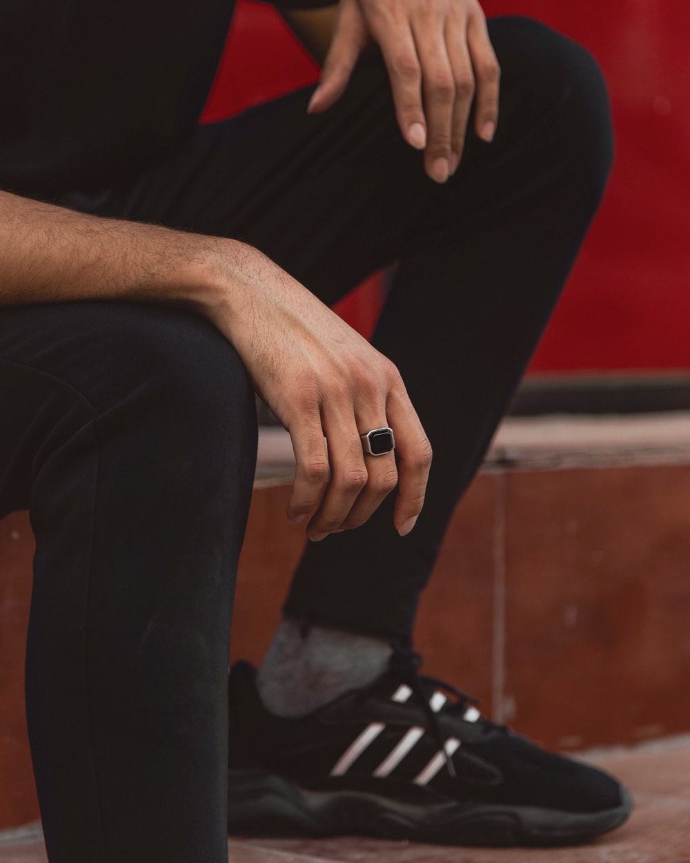 person in black pants sitting on brown wooden bench