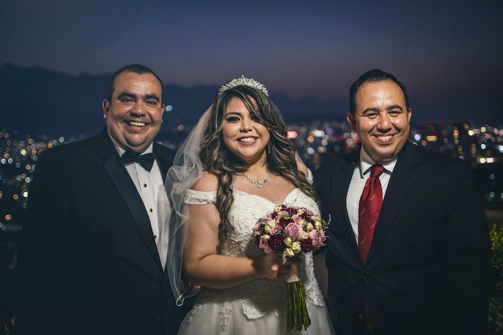 man in black suit jacket beside woman in white wedding dress