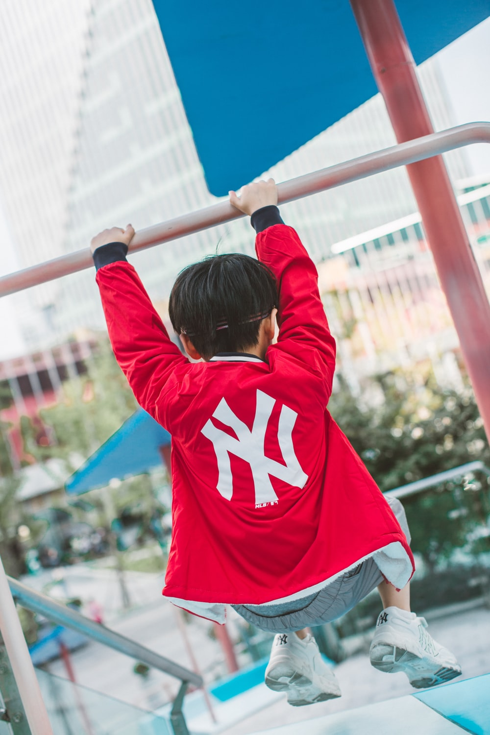 woman in red and white hoodie holding on blue metal bar during daytime