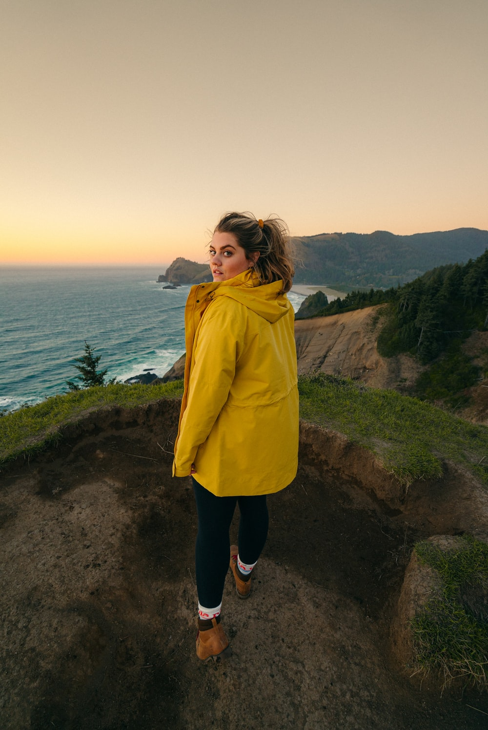 woman in yellow coat standing on brown dirt road near body of water during daytime