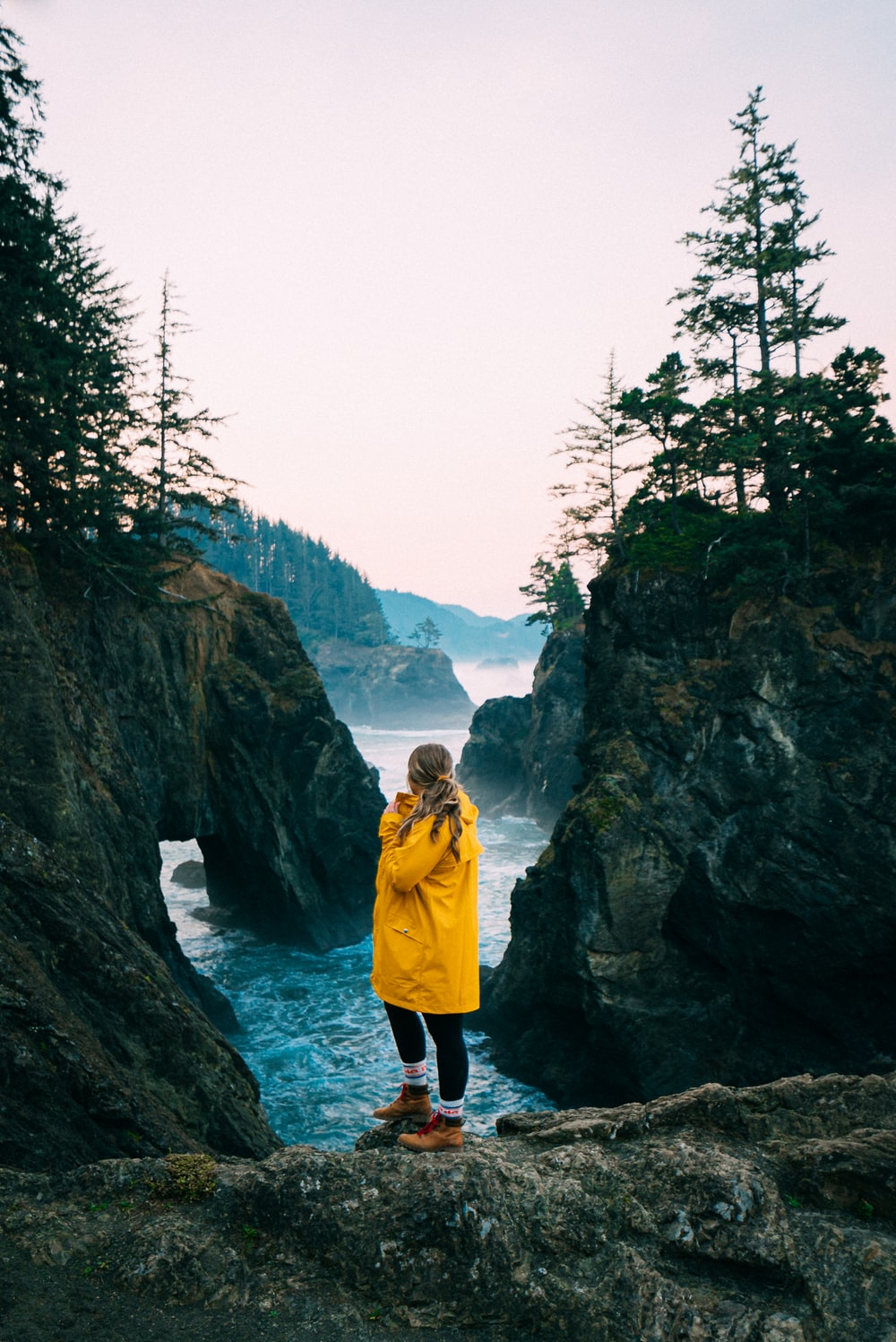 2 women standing on rock formation near body of water during daytime