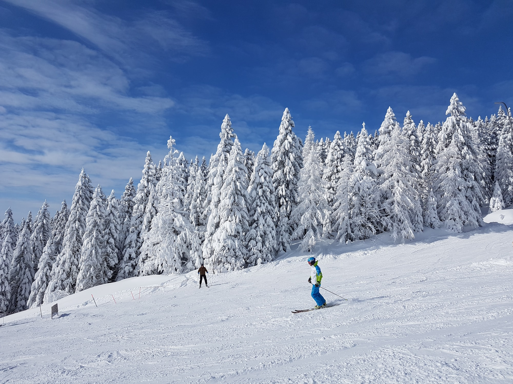 Skiers coming down the slopes in a ski resort in Slovenia.