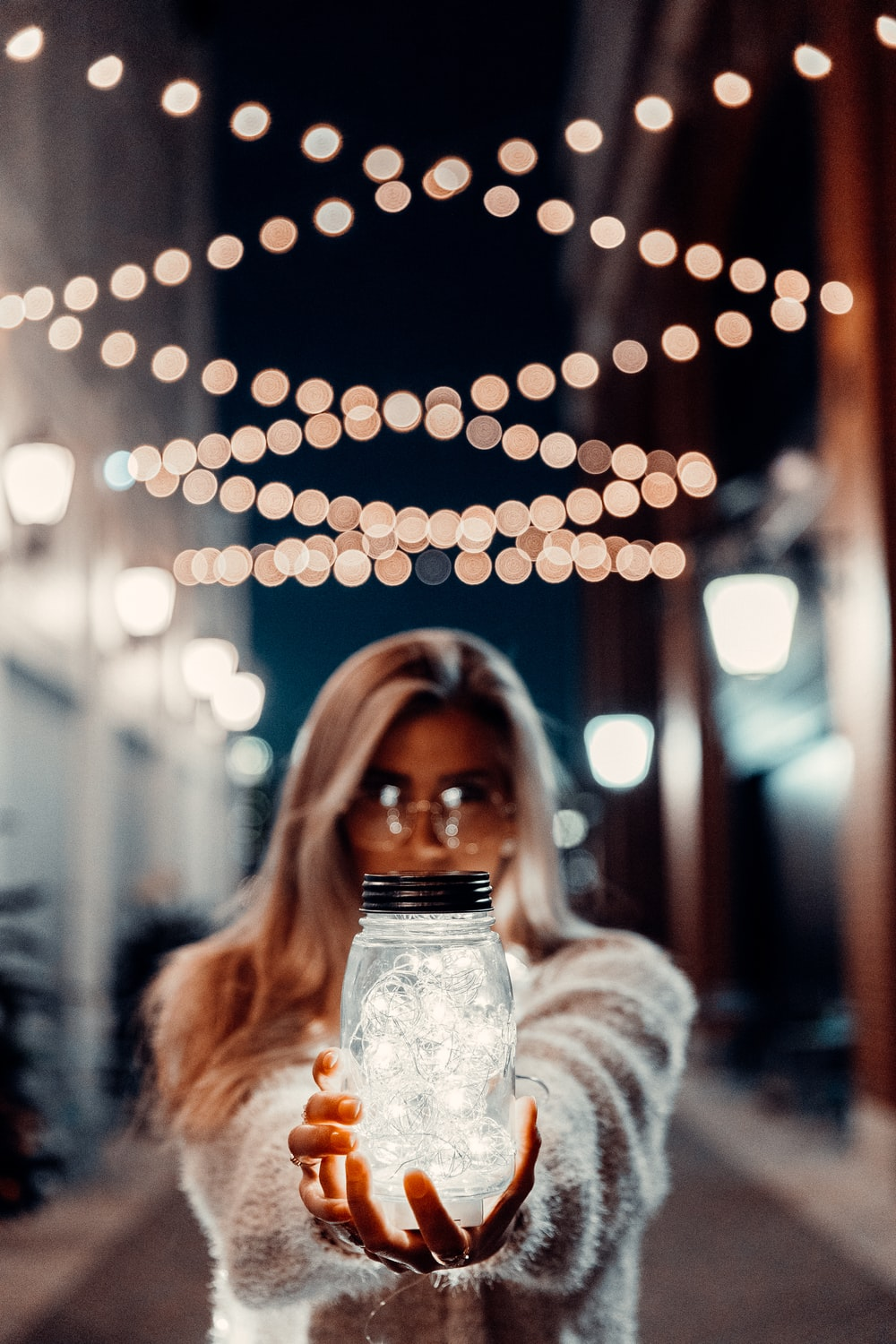 woman in white sweater holding clear glass jar