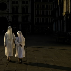 woman in white robe standing on brown brick floor during night time