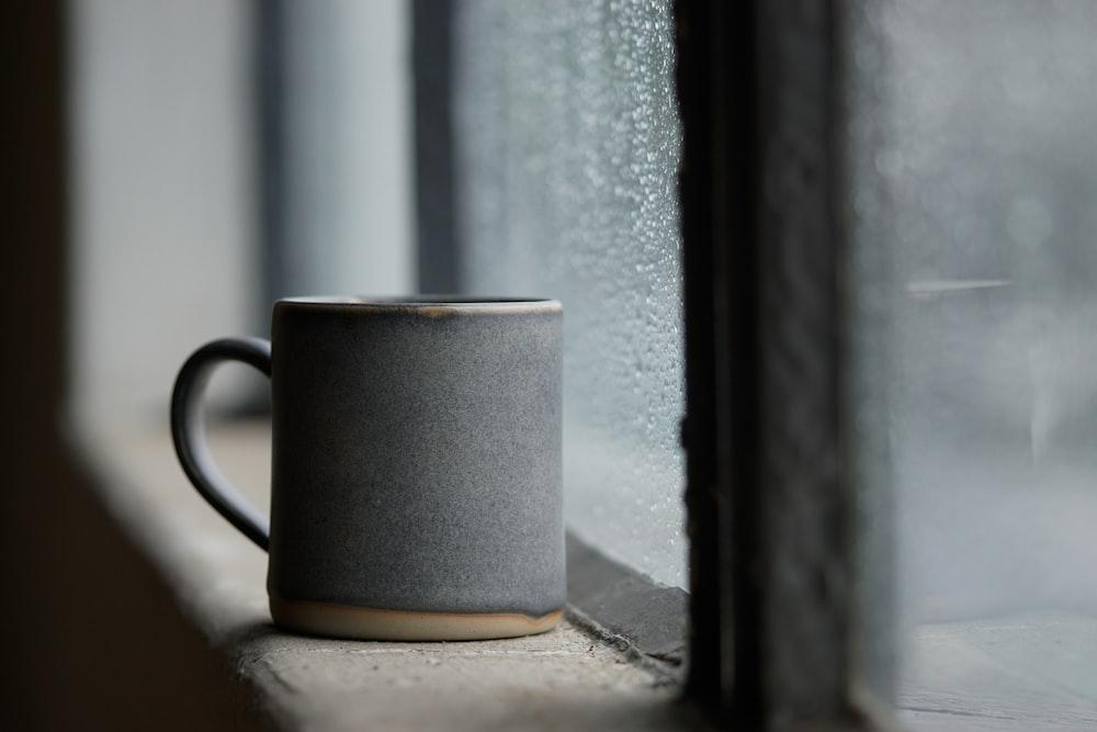 black ceramic mug on white concrete window