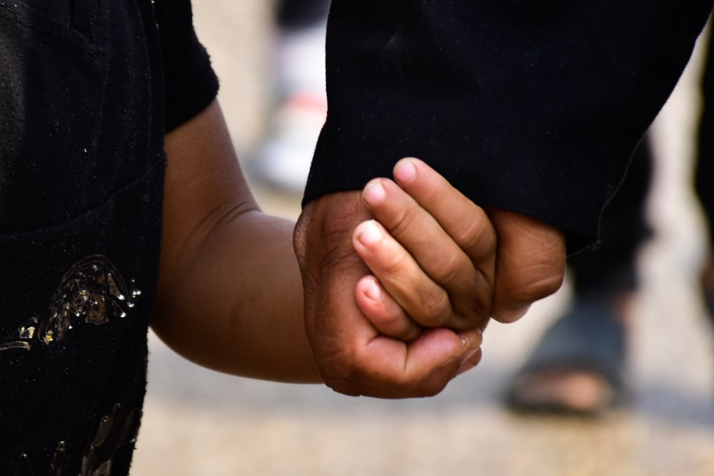person in black t-shirt holding persons hand
