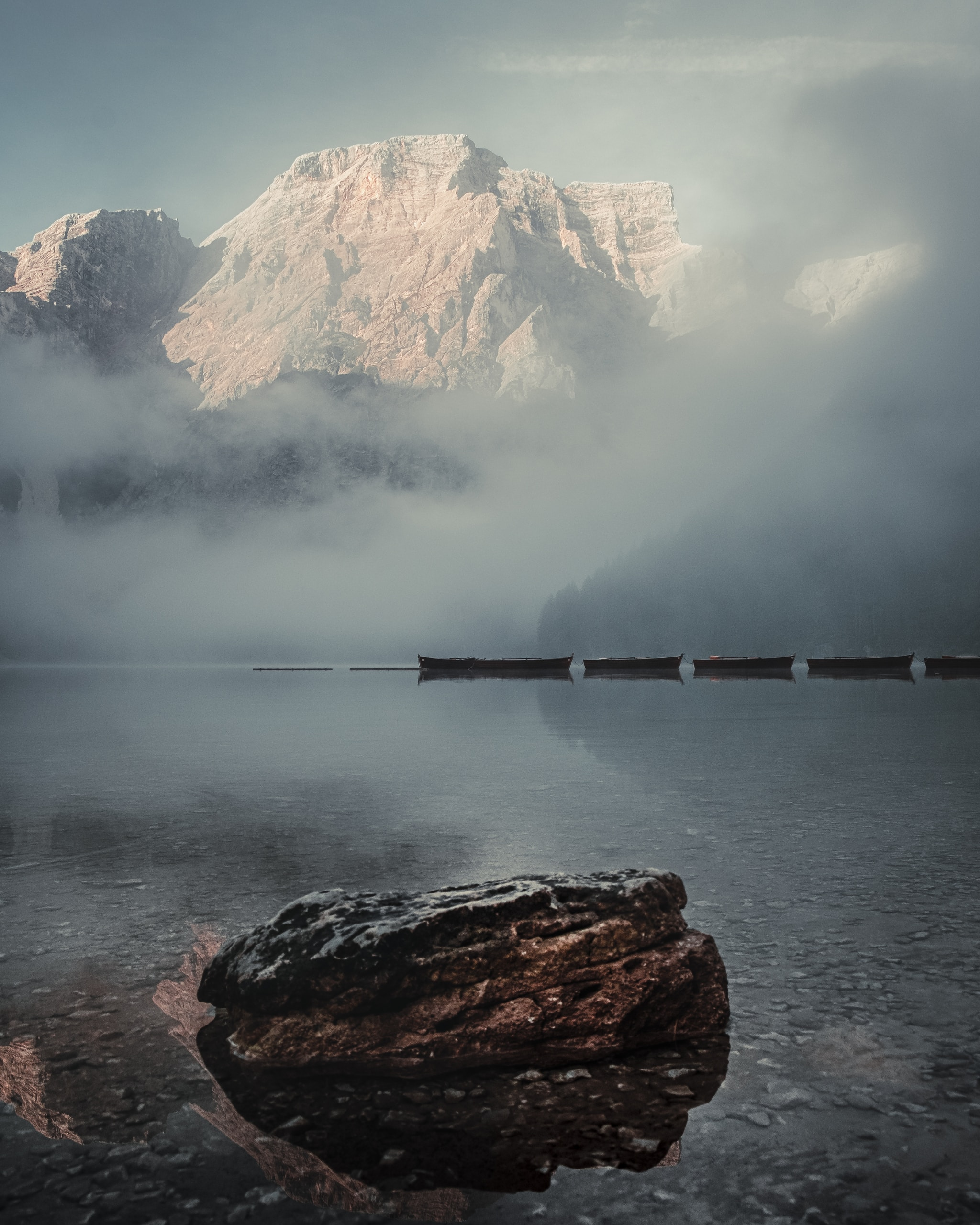 brown wooden dock on body of water near snow covered mountain during daytime