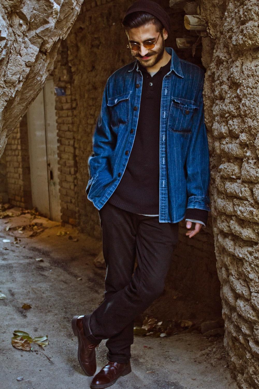 man in blue denim jacket standing beside brown brick wall