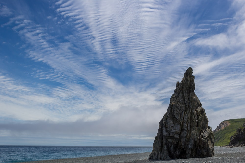 gray rock formation on sea shore under blue sky during daytime