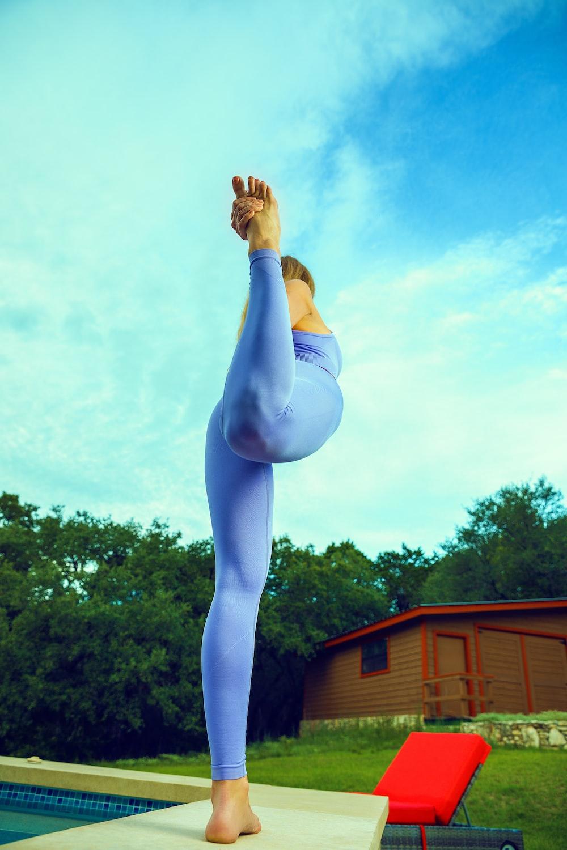 woman in blue leggings raising her both hands