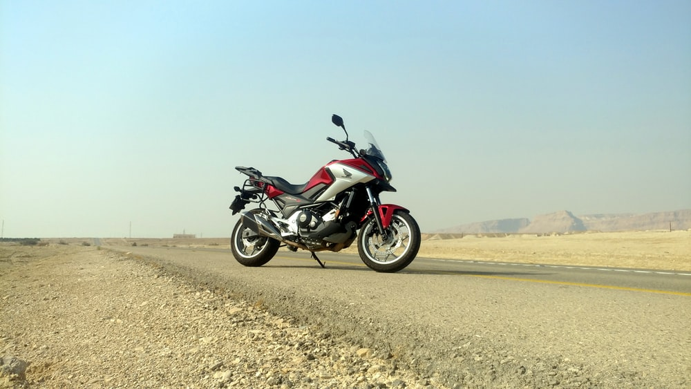 black and silver sports bike on brown field during daytime