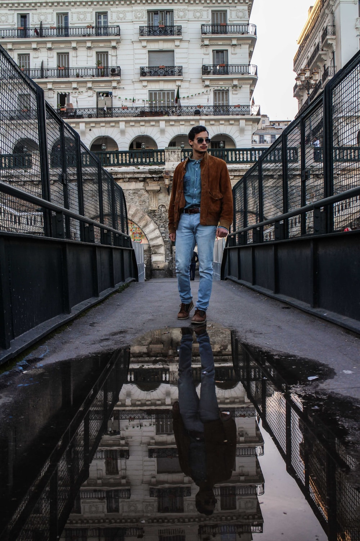 woman in blue denim jeans and orange jacket standing on bridge during daytime