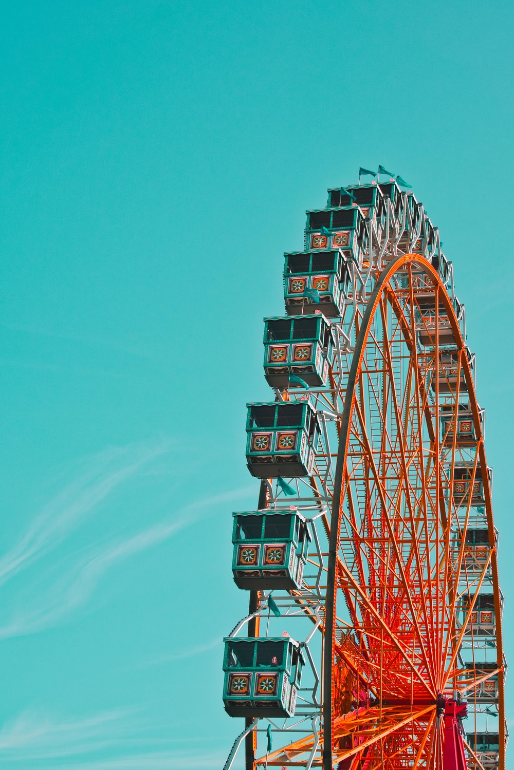 red and green ferris wheel under blue sky during daytime