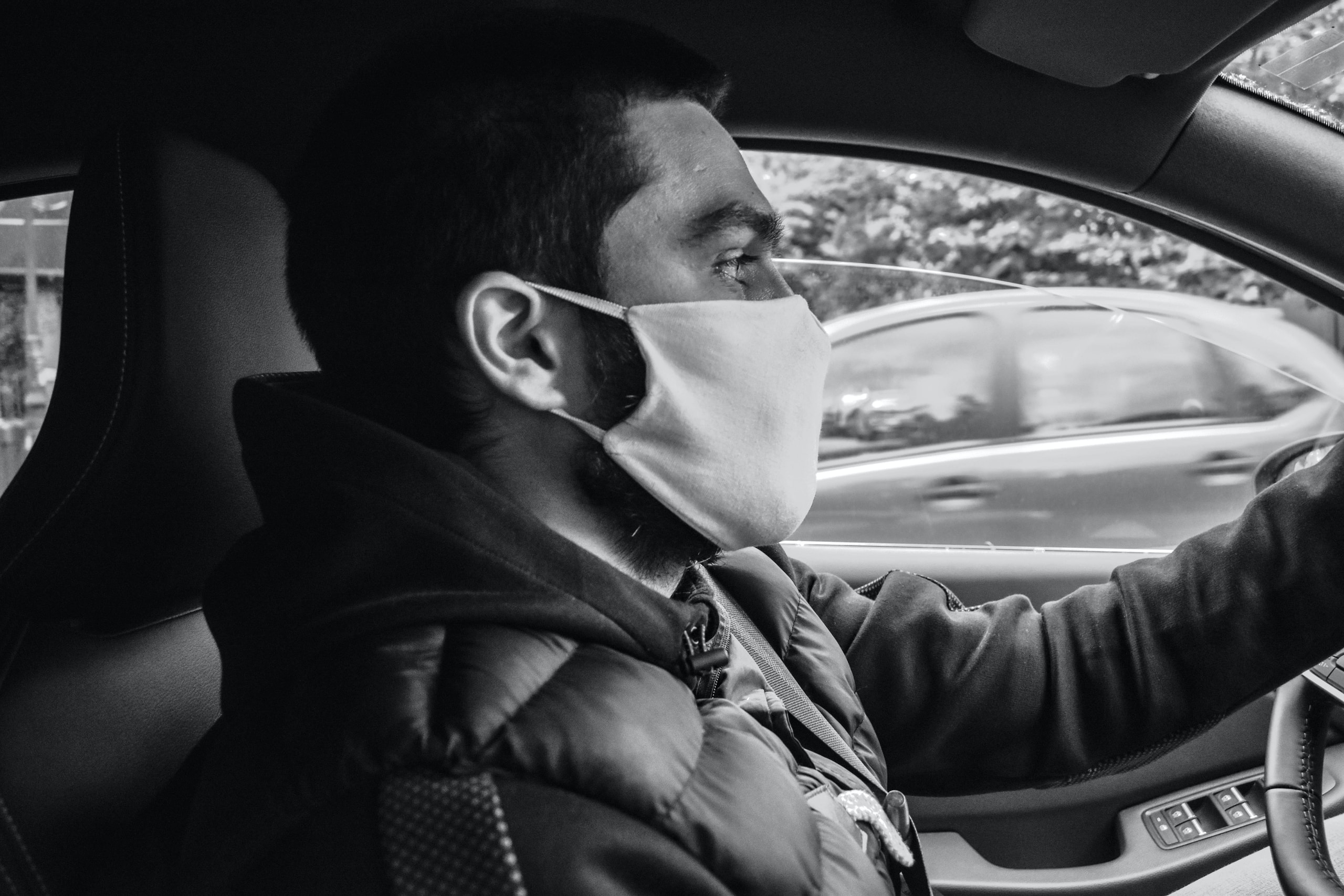 grayscale photo of man in jacket driving car