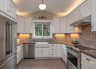white wooden kitchen cabinet with white pendant lamp