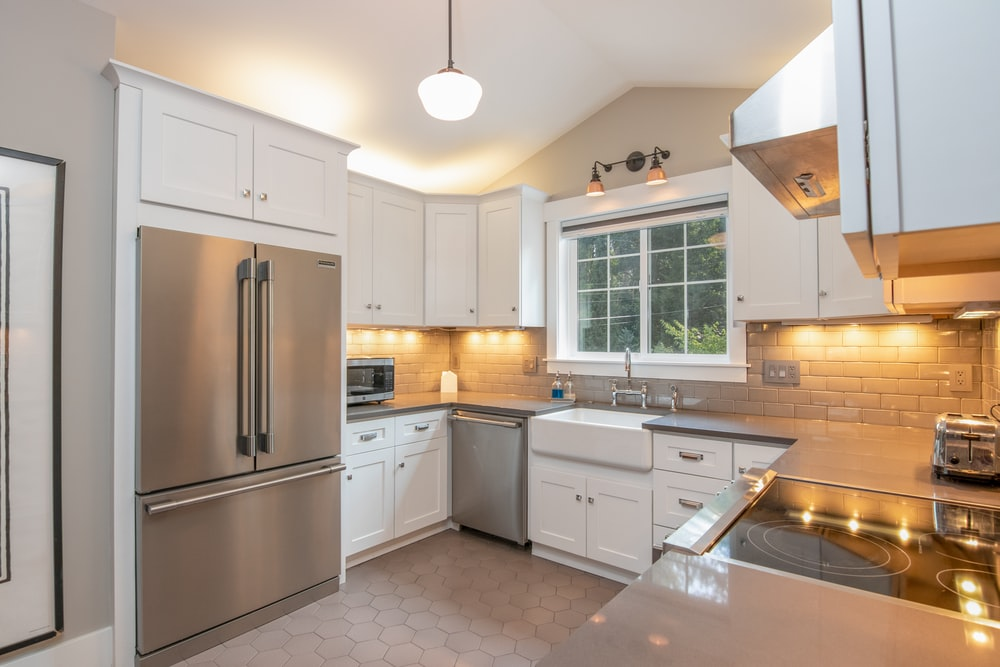 white wooden kitchen cabinet and white pendant lamp