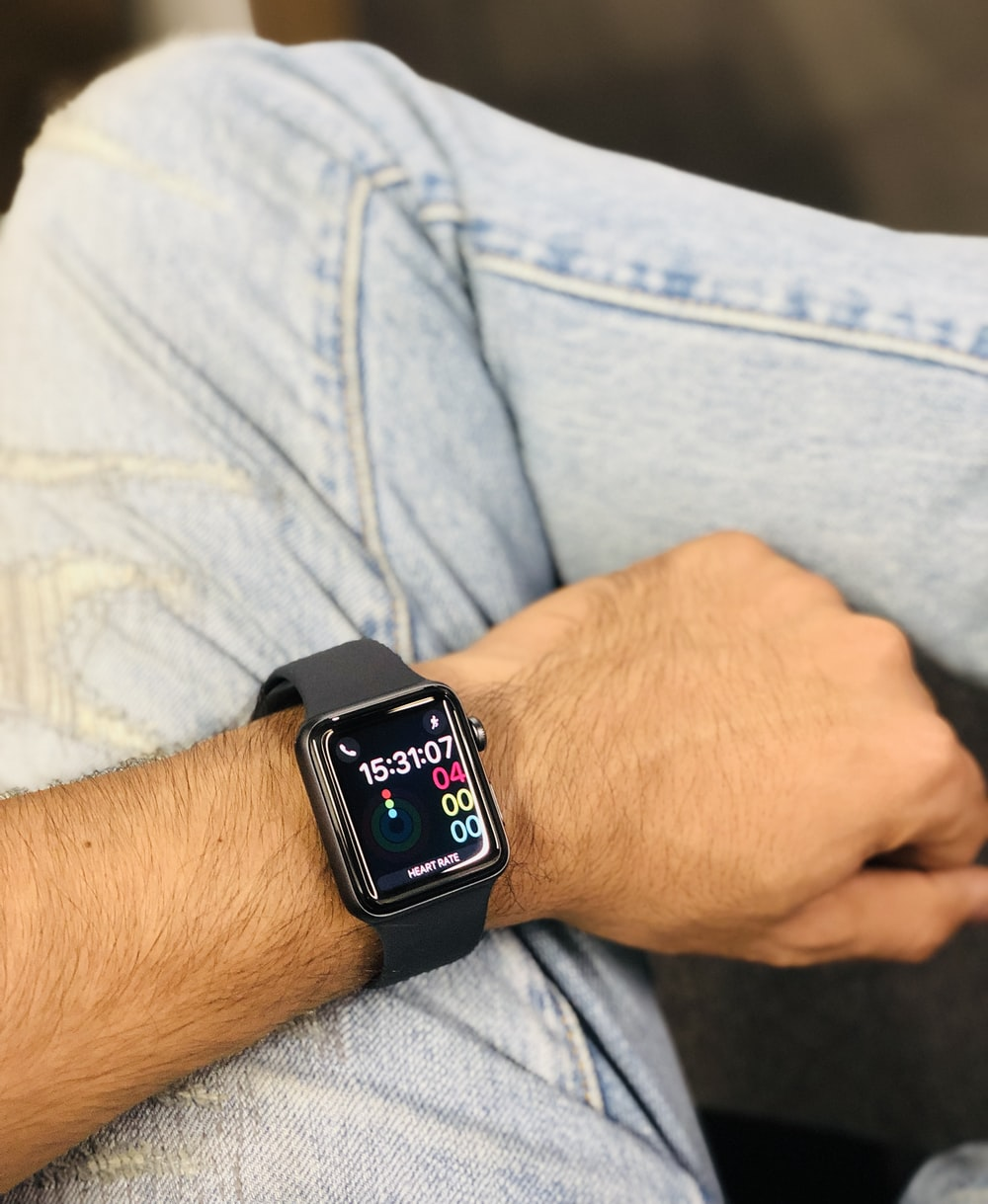 person wearing silver aluminum case apple watch with black sport band