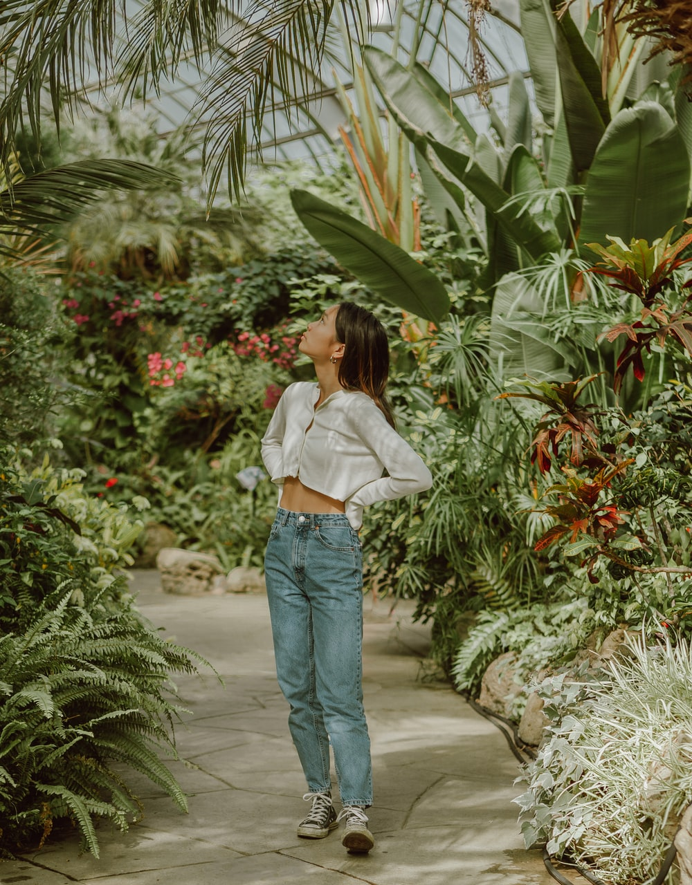 woman in white shirt and blue denim jeans standing near green plants during daytime