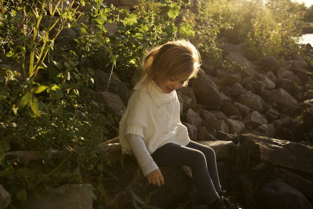 girl in white long sleeve shirt sitting on rock during daytime