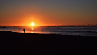 Wollongong silhouette of person standing on seashore during sunset