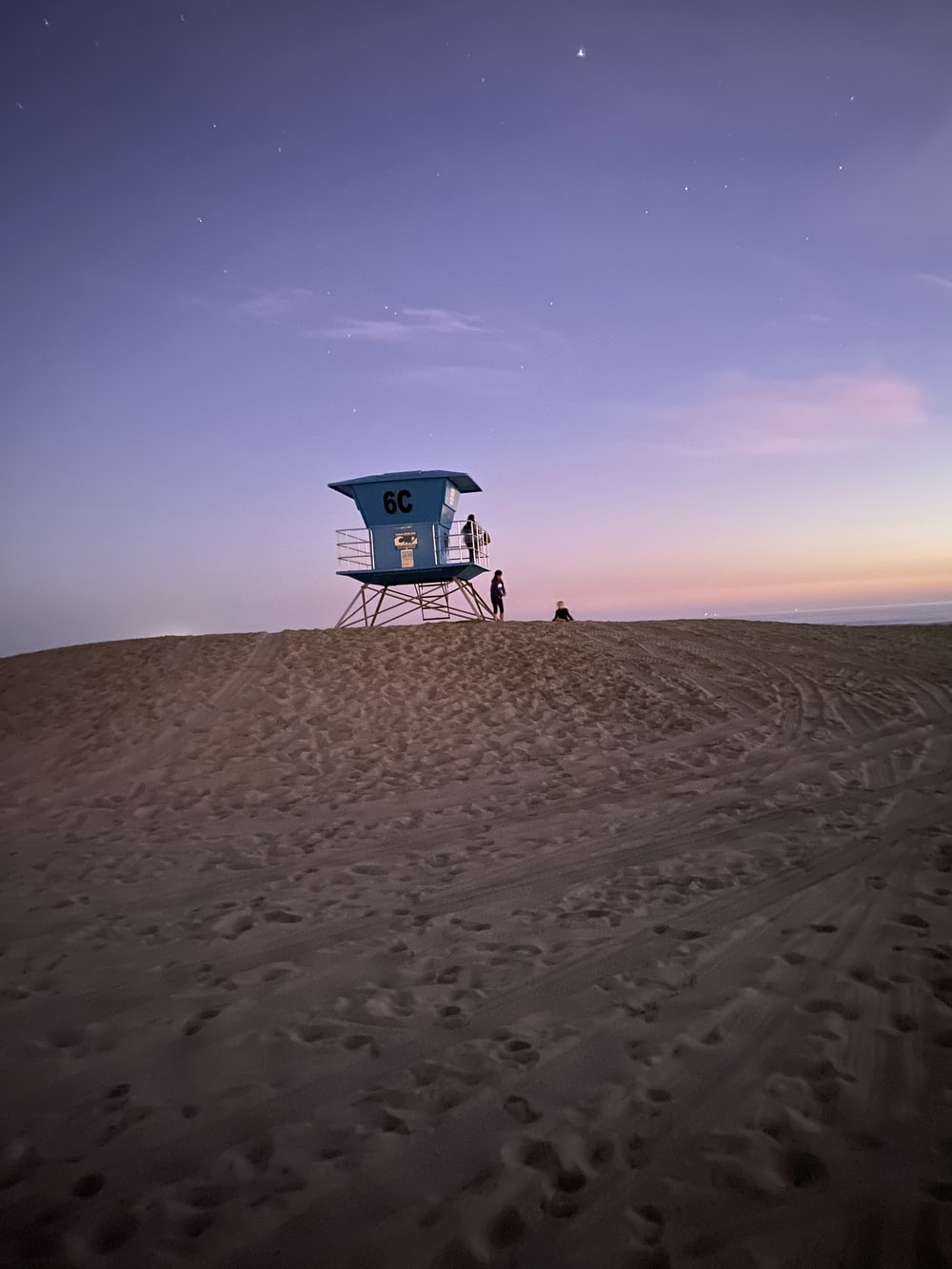 blue and white lifeguard house on sand