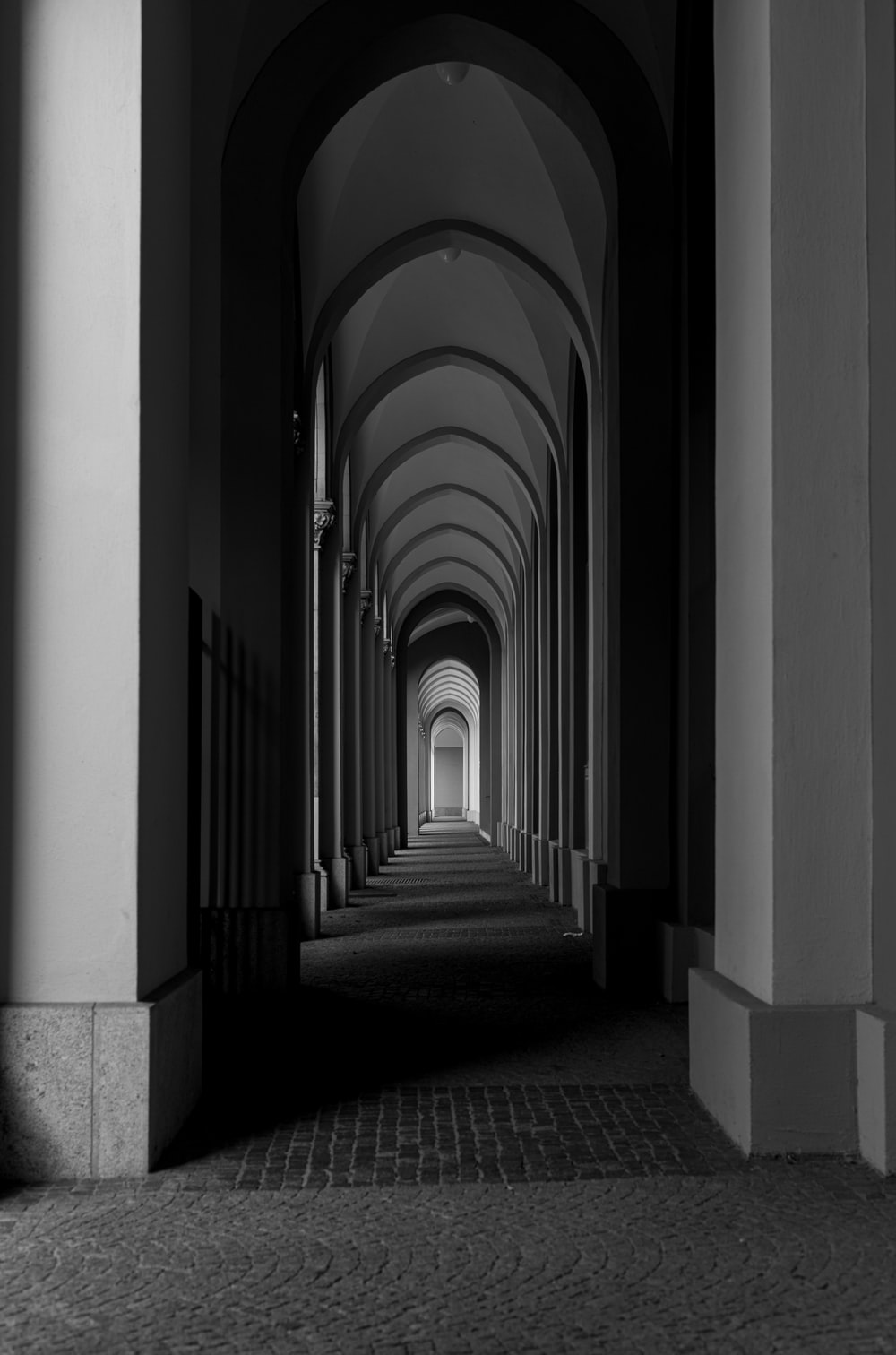grayscale photo of hallway with columns