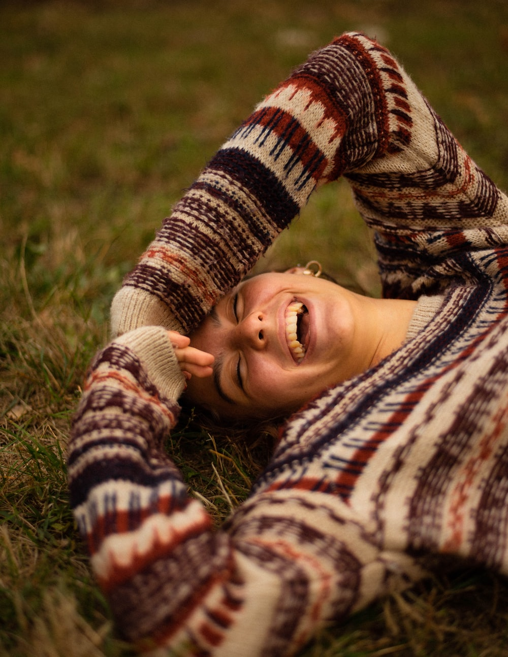 woman in brown and white sweater lying on green grass field during daytime