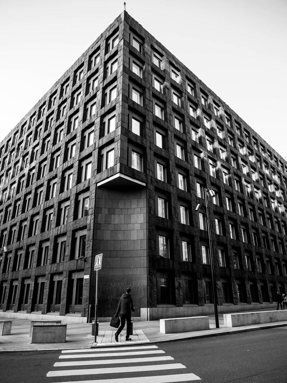 grayscale photo of man standing in front of building