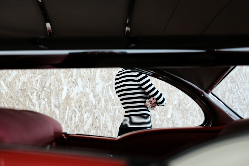 person in black and white striped long sleeve shirt sitting on red car seat
