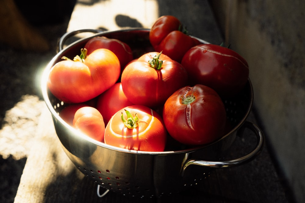 red tomatoes on stainless steel bowl