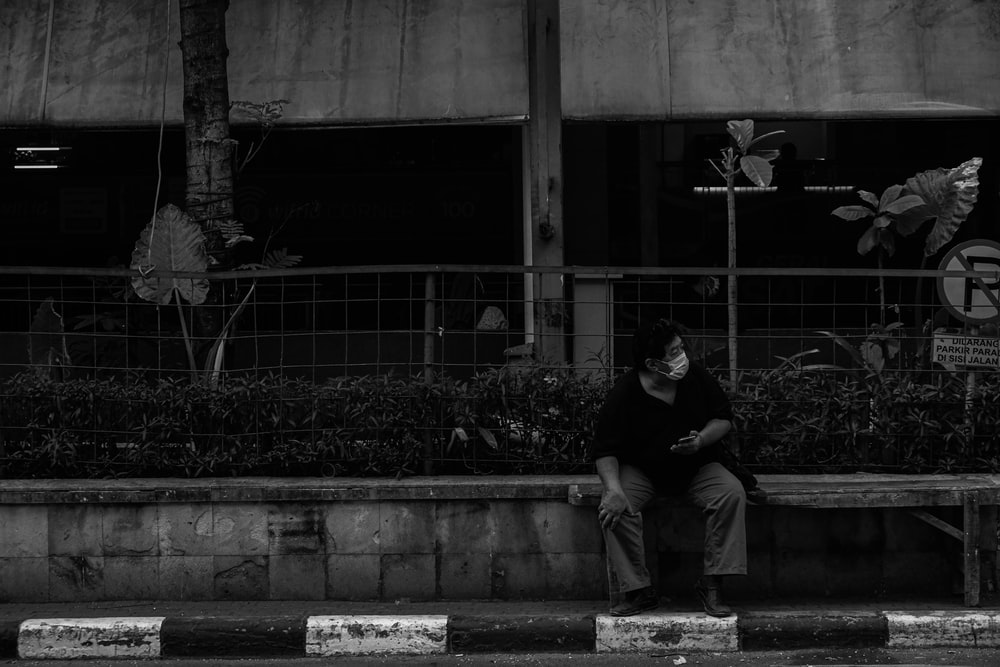 man in black crew neck t-shirt sitting on concrete bench